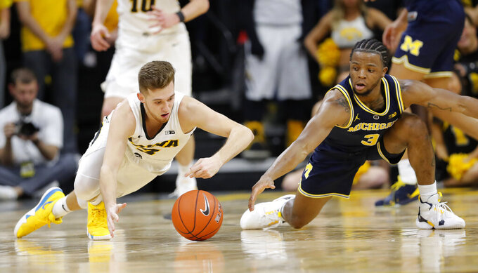 Iowa guard Jordan Bohannon, left, fights for a loose ball with Michigan guard Zavier Simpson during the first half of an NCAA college basketball game Friday, Feb. 1, 2019, in Iowa City, Iowa. (AP Photo/Charlie Neibergall)