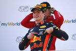 Red Bull driver Max Verstappen of the Netherlands celebrates on the podium after winning the Austrian Formula One Grand Prix at the Red Bull Ring racetrack in Spielberg, southern Austria, Sunday, June 30, 2019. In the background is second placed Ferrari driver Charles Leclerq of Monaco. (AP Photo/Ronald Zak)