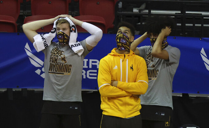 The Wyoming bench watches during the final minutes of the second half of an NCAA college basketball game against San Diego State in the quarterfinal round of the Mountain West Conference tournament Thursday, March 11, 2021, in Las Vegas. (AP Photo/Isaac Brekken)