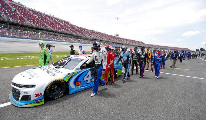 Los pilotos de NASCAR Kyle Busch (izquierda) y Corey LaJoie (derecha) acompañan a sus colegas y mecánicos al empujar el auto de Bubba Wallace al frente de la largada de la carrera de la Cup Series en  Talladega Alabama, el lunes 22 de junio de 2020.(AP Foto/John Bazemore)