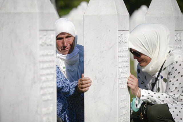 Women lean on a gravestone in Potocari, near Srebrenica, Bosnia, Saturday, July 11, 2020. Nine newly found and identified men and boys were laid to rest as Bosnians commemorate 25 years since more than 8,000 Bosnian Muslims perished in 10 days of slaughter, after Srebrenica was overrun by Bosnian Serb forces during the closing months of the country's 1992-95 fratricidal war, in Europe's worst post-WWII massacre. (AP Photo/Kemal Softic)