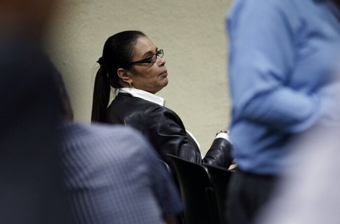 Guatemala's former Vice President Roxana Baldetti waits for the start of one of her several corruption trials in Guatemala City, Monday, Oct. 8, 2018. At this trial, Baldetti is accused of influencing the illegal awarding of a government contract to clean up lake pollution, and will learn if she's convicted or not. (AP Photo/Moises Castillo)