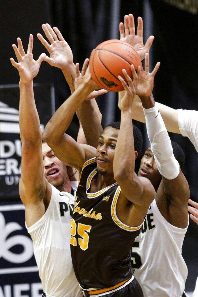Valparaiso guard Nick Robinson (25) looks for an open teammate as he is guarded by Purdue forward Mason Gillis (0) and guard Brandon Newman (5) during the first half of an NCAA college basketball game Friday, Dec. 4, 2020, in West Lafayette, Ind. (Nikos Frazier/Journal & Courier via AP)