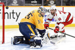A shot from Carolina Hurricanes left wing Jordan Martinook (48) misses the net past Nashville Predators goaltender Pekka Rinne (35) during the second period of an NHL hockey game in Nashville, Tenn., Monday, Jan. 18, 2021. (Andrew Nelles/The Tennessean via AP)