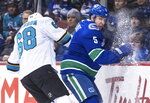 San Jose Sharks' Melker Karlsson, left, of Sweden, checks Vancouver Canucks' Derrick Pouliot during the first period of an NHL hockey game in Vancouver, British Columbia, on Monday, Feb. 11, 2019. (Darryl Dyck/The Canadian Press via AP)
