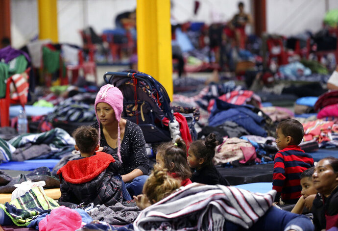 Honduran Delia Romero, 24, sits with her children in their sleeping area at a sheltered in Piedras Negras, Mexico, Tuesday, Feb. 5, 2019. A caravan of about 1,600 Central American migrants camped Tuesday in the Mexican border city of Piedras Negras, just west of Eagle Pass, Texas. The governor of the northern state of Coahuila described the migrants as