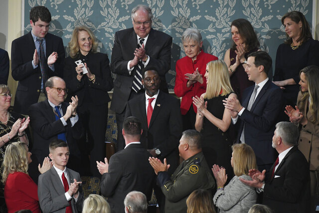 "In this Feb. 4, 2020, photo, Tony Rankins, center in red tie, receives a standing ovation during the State of the Union address to a joint session of Congress on Capitol Hill in Washington. Rankins, a formerly homeless, drug-addicted Army vet, got the standing ovation after President Donald Trump described how he turned his life around thanks to a construction job at a company using the administration's ""Opportunity Zone"" tax breaks targeting poor neighborhoods. Rankins, a tradesman who has indeed moved out of his car and into an apartment since landing the job refurbishing a Nashville hotel two years ago, doesn't work at a site using the tax breaks and never has. (AP Photo/Susan Walsh)"