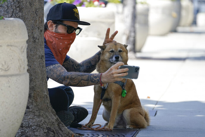 Andrew Stuart wears a bandana as a mask while taking a selfie with his dog, Voltron, on Sunset Blvd, Thursday, July 2, 2020, in West Hollywood, Calif. Sheriff's deputies in West Hollywood will issue citations to people who are not wearing masks in public, ramping up enforcement that previously had largely been imposed without penalties. (AP Photo/Ashley Landis)