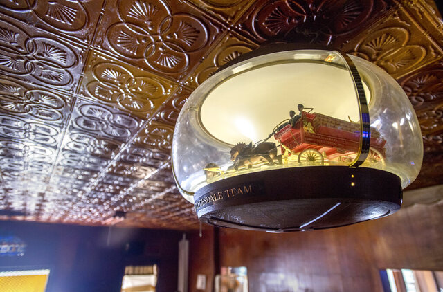 A vintage, rotating Budweiser Clydesdales lamp hangs from the tin ceiling at Mike's Tavern in West Peoria, Ill., Wednesday, Sept. 16, 2020. The timeworn saloon is one of the oldest in the Peoria area, brimming with the same casual atmosphere (and, maybe, some of the same dust) since its inception nine decades ago. Over its first 82 years, Mike's was owned by only two families, a streak that ended this month. (Matt Dayhoff/Journal Star via AP)