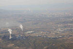 FILE - In this April 21, 2021, file photo, smoke and steam rise from towers at the coal-fired Urumqi Thermal Power Plant as seen from a plane in Urumqi in western China's Xinjiang Uyghur Autonomous Region. U.S. climate envoy John Kerry came to China seeking to press the world's largest emitter of greenhouse gases to do more in the global effort to hold down the rise in temperature. What he got was renewed demands for Washington to change its stance toward China on a host of other issues from human rights to Taiwan. (AP Photo/Mark Schiefelbein, File)