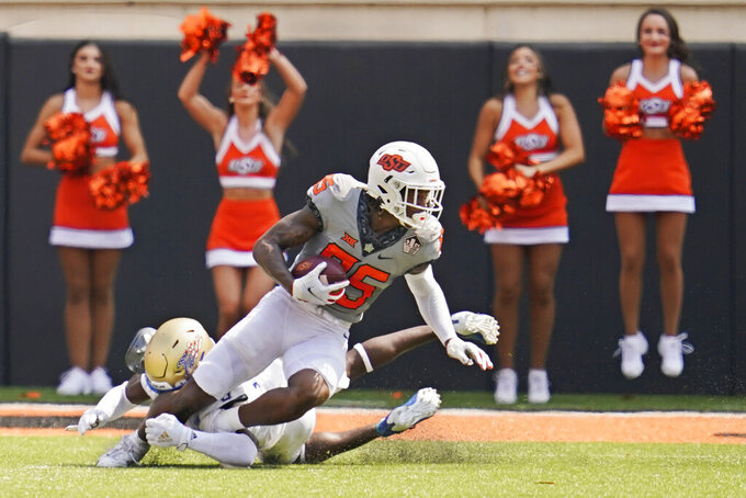 Oklahoma State wide receiver Jaden Bray (85) avoids a tackle by Tulsa cornerback Tyon Davis, left, and takes a Spencer Sanders pass in for a touchdown in the first half of an NCAA college football game, Saturday, Sept. 11, 2021, in Stillwater, Okla. (AP Photo/Sue Ogrocki)