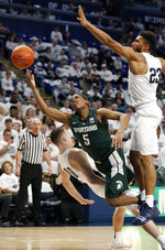 Michigan State's Cassius Winston (5) drives to the hoop as he is fouled by Penn State's Kyle McCloskey (10) during first-half action of an NCAA college basketball game in State College, Pa. Sunday, Jan. 13, 2019. (AP Photo/Chris Knight)