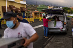 Residents remove their belongings from their houses as lava from a volcano eruption flows, as they are evacuated from their village in Los Llanos, on the island of La Palma in the Canaries, Spain, Wednesday, Sept. 22, 2021. A volcano on a small Spanish island in the Atlantic Ocean erupted on Sunday, forcing the evacuation of thousands of people. Experts say the volcanic eruption and its aftermath on a Spanish island could last for up to 84 days. The Canary Island Volcanology Institute said Wednesday it based its calculation on the length of previous eruptions on the archipelago. (AP Photo/Emilio Morenatti)