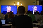Journalists look at screens showing Russian President Vladimir Putin as he answers a question during his annual call-in show in Moscow, Russia, Thursday, June 20, 2019. Putin hosts call-in shows every year, which typically provides a platform for ordinary Russians to appeal to the president on issues ranging from foreign policy to housing and utilities. (AP Photo/Alexander Zemlianichenko)