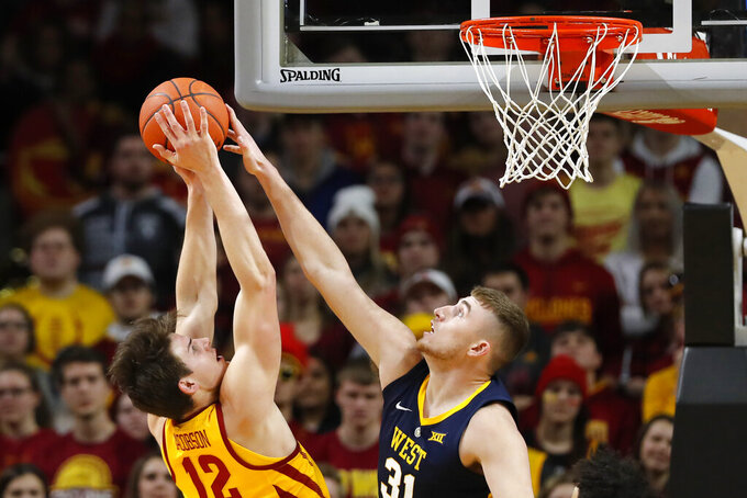 West Virginia forward Logan Routt blocks a shot by Iowa State forward Michael Jacobson, left, during the first half of an NCAA college basketball game Wednesday, Jan. 30, 2019, in Ames, Iowa. (AP Photo/Charlie Neibergall)