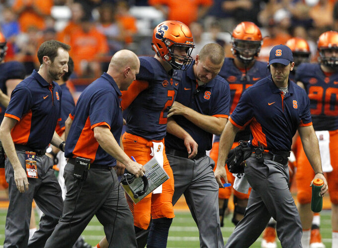 FILE - In this Sept. 19, 2015, file photo, Syracuse's Eric Dungey, center, is helped off the field after being injured by a helmet-to-helmet hit from Central Michigan defensive lineman Mitch Stanitzek on a play in the second quarter of an NCAA college football game in Syracuse, N.Y. The hit sidelined Dungey for three weeks. Dungey says the stigma of his injuries in college has hampered his chances of playing professionally. (AP Photo/Nick Lisi, File)