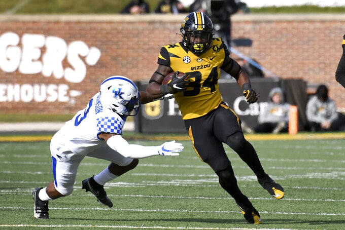 Missouri running back Larry Rountree III (34) runs with the ball as Kentucky defensive back Davonte Robinson defends during the first half of an NCAA college football game Saturday, Oct. 24, 2020, in Columbia, Mo. (AP Photo/L.G. Patterson)