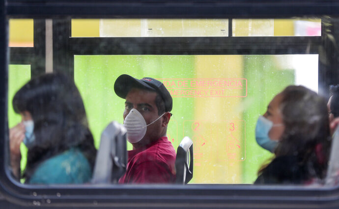 Commuters wear masks as they ride a bus, to prevent the spread of the new coronavirus in Mexico City, Tuesday, March 31, 2020. Mexico's government has broadened its shutdown of