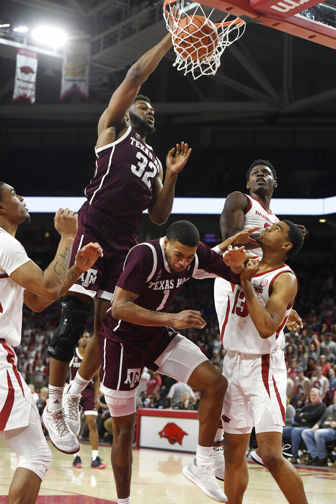Texas A&M forward Josh Nebo (32) dunks over Arkansas defenders Mason Jones (13) and Adrio Bailey (back) during the second half of an NCAA college basketball game, Saturday, Feb. 23, 2019 in Fayetteville, Ark. (AP Photo/Michael Woods)