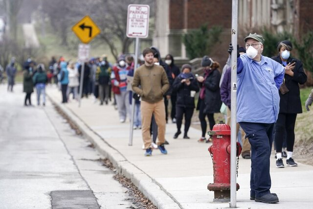 FILE - In this April 7, 2020 file photo, voters observe social distancing guidelines as they wait in line to cast ballots in the presidential primary election in Milwaukee. More than 50 people who voted in person or worked the polls during Wisconsin's election earlier this month have tested positive for COVID-19 so far. But there are no plans to move or otherwise alter a special congressional election coming in less than two weeks. (AP Photo/Morry Gash File)