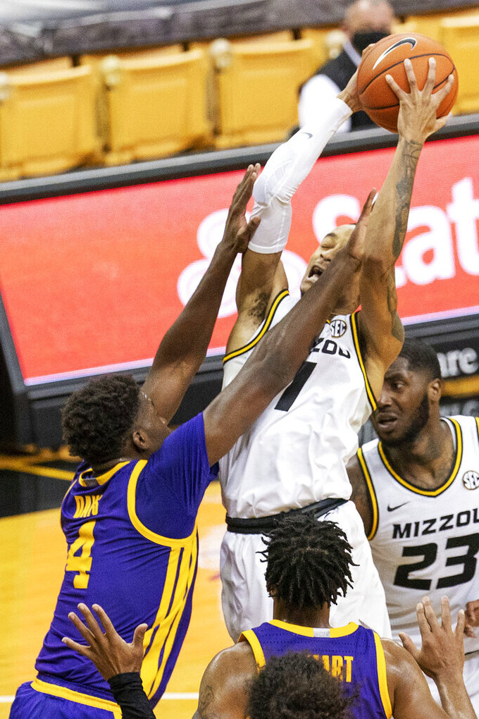 Missouri's Xavier Pinson, right, shoots as he is fouled by LSU's Darius Days, left, during the second half of an NCAA college basketball game Saturday, March 6, 2021, in Columbia, Mo.  (AP Photo/L.G. Patterson)