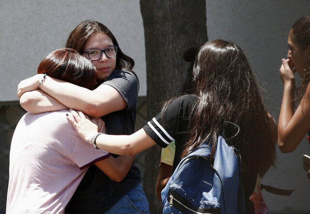 Relatives of passengers of a missing military plane comfort each other as they arrive at the Cerrillos airbase in Santiago, Chile, Tuesday, Dec. 10, 2019. Chile's air force said it lost radio contact with a C-130 Hercules transport plane carrying 38 people on a flight to the country's base in Antarctica, and authorities are indicating they are not optimistic about the aircraft's fate. (AP Photo/Luis Hidalgo)