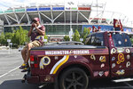 "Rodney Johnson of Chesapeake, Va., sits on the back of his truck outside FedEx Field in Landover, Md., Monday, July 13, 2020. The Washington NFL franchise announced Monday that it will drop the ""Redskins"" name and Indian head logo immediately, bowing to decades of criticism that they are offensive to Native Americans. (AP Photo/Susan Walsh)"