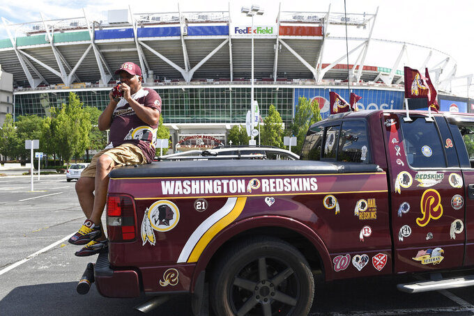 """Rodney Johnson of Chesapeake, Va., sits on the back of his truck outside FedEx Field in Landover, Md., Monday, July 13, 2020. The Washington NFL franchise announced Monday that it will drop the """"Redskins"""" name and Indian head logo immediately, bowing to decades of criticism that they are offensive to Native Americans. (AP Photo/Susan Walsh)"""