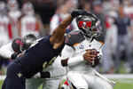 Tampa Bay Buccaneers quarterback Jameis Winston avoids a sack under pressure from New Orleans Saints defensive end Marcus Davenport in the first half of an NFL football game in New Orleans, Sunday, Oct. 6, 2019. (AP Photo/Gerald Herbert)