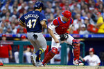 Philadelphia Phillies catcher J.T. Realmuto, right, forces out Milwaukee Brewers' Gio Gonzalez at home on a ball hit by Ryan Braun during the third inning of a baseball game Wednesday, May 15, 2019, in Philadelphia. (AP Photo/Matt Slocum)