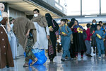 People evacuated from Kabul, Afghanistan, walk through the terminal before boarding a bus after they arrived at Washington Dulles International Airport, in Chantilly, Va., on Thursday, Sept. 2, 2021. (AP Photo/Jose Luis Magana)