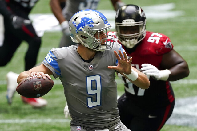 Detroit Lions quarterback Matthew Stafford (9) works in the pocket under pressure by Atlanta Falcons defensive tackle Grady Jarrett (97) during the first half of an NFL football game, Sunday, Oct. 25, 2020, in Atlanta. (AP Photo/John Bazemore)