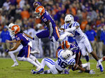 FILE - In this Nov. 17, 2018, file photo, Clemson's Derion Kendrick (10) hurdles Duke's Chris Rumph ll (96) on a kickoff return as Jarrett Garner reaches for him during the first half of an NCAA college football game in Clemson, S.C. Kickoff returns are down about 20 percent in the first year of a new NCAA rule that gives the receiving team possession at its 25-yard line if the kick is fair caught anywhere between the goal line and 25. (AP Photo/Richard Shiro, File)