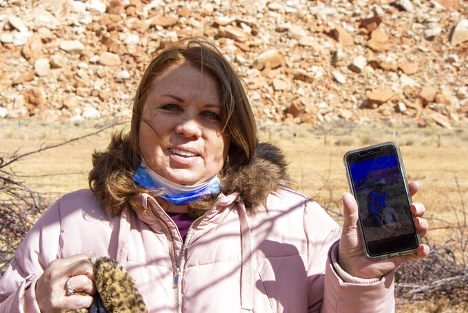 Liz Pace poses with a photo of her grandfather Worthen Jackson, a caretaker of the Capitol Reef Orchards over 50 years ago, on Thursday, March 4, 2021, at Capitol Reef National Park, in Fruita, Utah. Pace, came to Capitol Reef National Park orchards to discuss a proposed orchard rehabilitation plan. (K. Sophie Will/The Spectrum via AP)