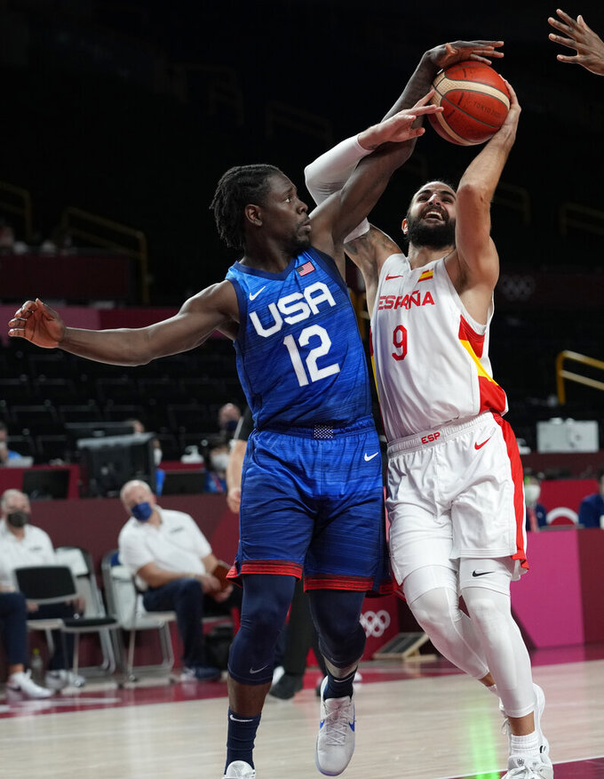 Spain's Ricky Rubio (9), right, and United States' Jrue Holiday (12) fight for the ball during men's basketball quarterfinal game at the 2020 Summer Olympics, Tuesday, Aug. 3, 2021, in Saitama, Japan. (AP Photo/Eric Gay)