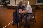 In this Monday, June 22, 2020 photo, Agustina Canamero, 81, and Pascual Pérez, 84, hug and kiss through a plastic film screen to avoid contracting the new coronavirus at a nursing home in Barcelona, Spain. Even when it comes wrapped in plastic, a hug can convey tenderness and relief, love and devotion. The fear that gripped Agustina Cañamero during the 102 days she and her 84-year-old husband spent physically separated during Spain's coronavirus outbreak dissolved the moment the couple embraced through a screen of plastic film. (AP Photo/Emilio Morenatti)