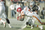 FILE - Kansas City Chiefs' running back Marcus Allen crosses the goal line for a third quarter touchdown as Los Angeles Raiders' Eddie Anderson tries to stop him in Los Angeles, in this Nov. 14, 1993, file photo. The Chiefs won, 31-20. A league MVP and Super Bowl winner with the Raiders, Allen left in 1993 when team owner Al Davis insisted he be a backup in a nasty feud with the player. Allen landed in Kansas City (Joe Montana already had arrived from the 49ers) and despite a mediocre performance he helped the Chiefs to a Game 4 home victory. (AP Photo/Eric Draper, File)