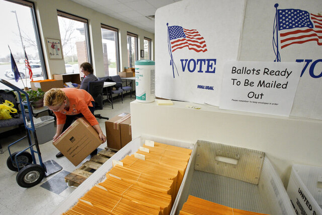In this April 14, 2020 photo, Nadette Cheney picks up a box of printed ballots as others work on preparing mail-in ballots at the Lancaster County Election Committee offices in Lincoln, Neb. Officials in Nebraska are forging ahead with plans for the state's May 12 primary despite calls from Democrats to only offer voting by mail and concerns from public health officials that in-person voting will help the coronavirus spread.  (AP Photo/Nati Harnik)