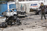 A Somali soldier guards the wreckage after a car bomb attack at a Presidential Palace checkpoint in Mogadishu, Somalia, Saturday Sept. 25, 2021. Police said a vehicle laden with explosives rammed into cars and trucks at a checkpoint leading to the entrance of the Presidential Palace, killing at least eight people. (AP Photo/Farah Abdi Warsameh)
