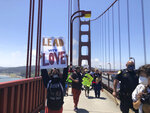 Dozens of people gathered by the Golden Gate Bridge Welcome Center in San Francisco Saturday, June 6, 2020, and march across the famous span in support of the Black Lives Matter movement. People are protesting the death of George Floyd, who died after he was restrained by Minneapolis police on May 25 in Minnesota. (AP Photo/Jeff Chiu)