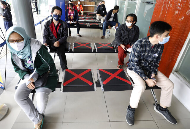 People sit spaced apart as they wait for a coronavirus test required to board long-distance trains the at Senen Train Station in Jakarta, Indonesia, Monday, July 27, 2020. Indonesia announced Monday that its confirmed number of coronavirus cases has surpassed 100,000, the most in Southeast Asia, as an official said the government still doesn't know when the outbreak will peak. (AP Photo/Dita Alangkara)