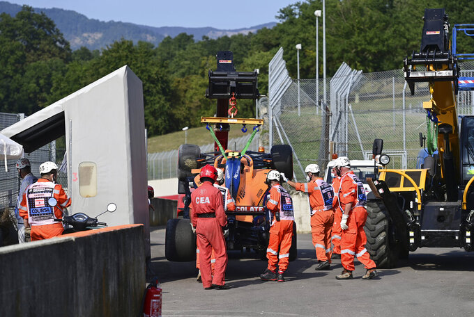 Track workers remove the car from the track of Mclaren driver Lando Norris of Britain during the second practice session ahead of the Grand Prix of Tuscany, at the Mugello circuit in Scarperia, Italy, Friday, Sept. 11, 2020. The Formula One Grand Prix of Tuscany will take place on Sunday. (Miguel Medina, Pool Photo via AP)