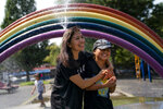Monica Muquinche and her son Sebastian plan in a sprinkler at a playground in their neighborhood in the Brooklyn borough of New York, Thursday, Aug. 26, 2021. Muquinche, whose husband disappeared in 2020 while trying to reach the U.S., is part of an extraordinary wave of Ecuadorians coming in the United States. (AP Photo/John Minchillo)