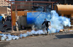 An anti-government protester is overcome by tear gas fired by riot police during the clashes, in Khilani Square, Baghdad, Iraq, Wednesday, Nov. 13, 2019. (AP Photo/Khalid Mohammed)