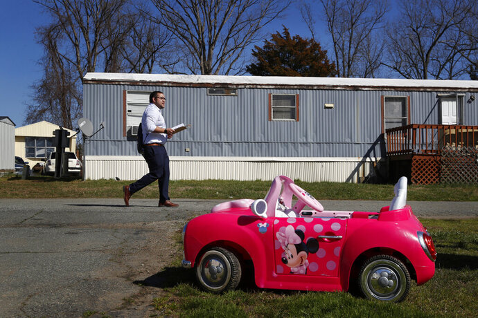 Ricky Hurtado, a Democratic candidate for the North Carolina state house, walks past a child's toy car as he canvasses in a largely Latino trailer community, in Burlington, N.C., Sunday, March 8, 2020. (AP Photo/Jacquelyn Martin)