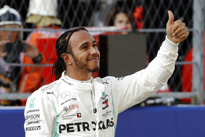 "FILE - In this Saturday, Sept. 28, 2019, file photo, Mercedes driver Lewis Hamilton, of Britain, celebrates after setting the second fastest time at the end of the qualifying session practice at the ""Sochi Autodrom"" Formula One circuit, in Sochi, Russia. Hamilton returns to Mexico City with a chance to clinch another Formula One championship. He's clinched the last two championships at the Mexican Grand Prix but hasn't finished on the podium there since winning in 2016. (AP Photo/Luca Bruno, File)"
