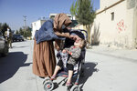 A health worker administers a polio vaccine to a child during a polio vaccination campaign in the city of Kabul, Afghanistan, Tuesday, March 30, 2021. (AP Photo/Rahmat Gul)