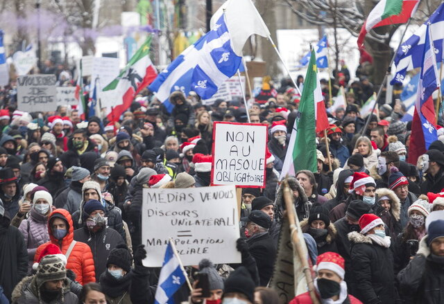 People participate in a demonstration in Montreal, Sunday, Dec. 20, 2020, protesting measures implemented by the Quebec government to help stop the spread of COVID-19. The COVID-19 pandemic continues in Canada and around the world. (Graham Hughes/The Canadian Press via AP)