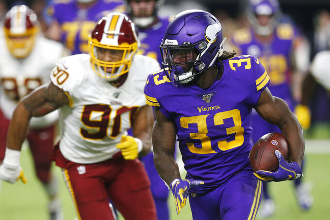 Minnesota Vikings running back Dalvin Cook (33) runs from Washington Redskins linebacker Montez Sweat (90) during the second half of an NFL football game, Thursday, Oct. 24, 2019, in Minneapolis. (AP Photo/Jim Mone)