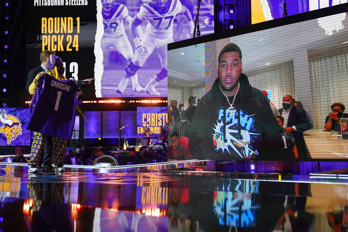 A Minnesota Vikings fan, left, holds a team jersey as an image of offensive lineman Christian Darrisaw is shown on stage after Darrisaw was chosen with the team with the 23rd pick in the first round of the NFL football draft, Thursday, April 29, 2021, in Cleveland. (AP Photo/Tony Dejak)